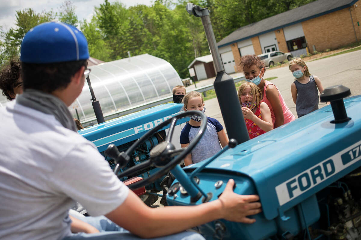 Coleman High School sophomore Hunter Harsh takes questions about his tractor from Coleman Elementary School students after participating in