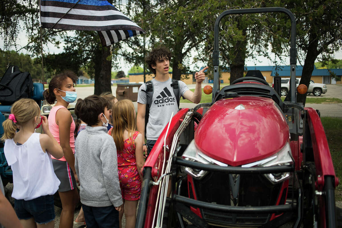Coleman High School sophomore Isaiah Biers, right, talks about a tractor with Coleman Elementary School students after participating in