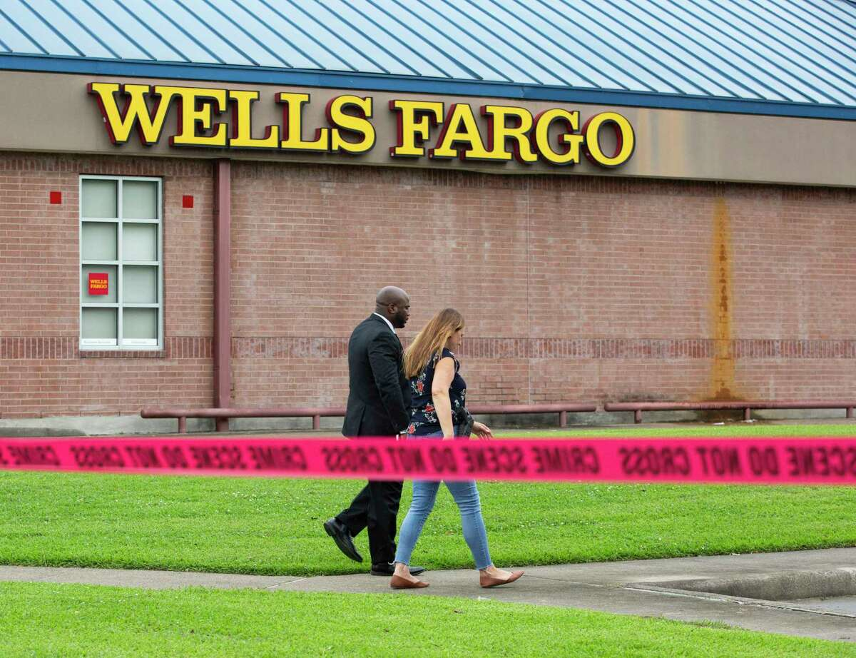 Houston Police Department detectives investigate a robbery and shooting at a Wells Fargo bank in the 9300 block of the Eastex Freeway Friday, May 21, 2021, in Houston.