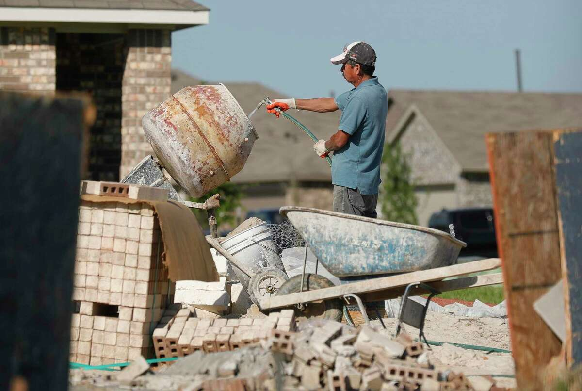 A man prepares a concrete mixer in a newly built neighborhood in Granger Pines, Tuesday, April 20, 2021, in Grangerland.