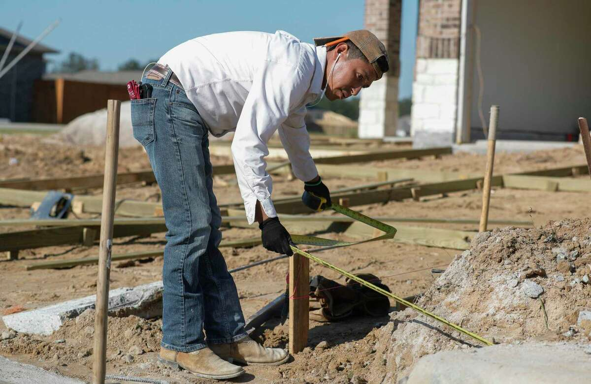 Leo Gonzales measures wood for driveway framing in a newly built neighborhood in Granger Pines, Tuesday, April 20, 2021, in Grangerland.