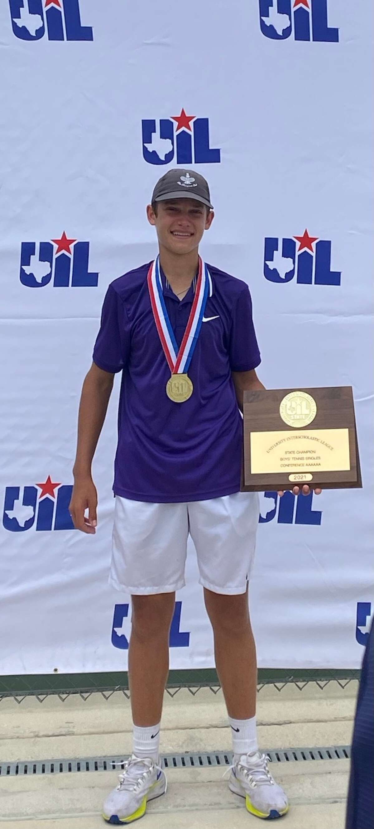 Midland High senior Tyler Stewart wears his gold medal and holds his championship plaque after winning the Class 6A boys singles state title at the UILTennis State Tournament, May 21 in Helotes.