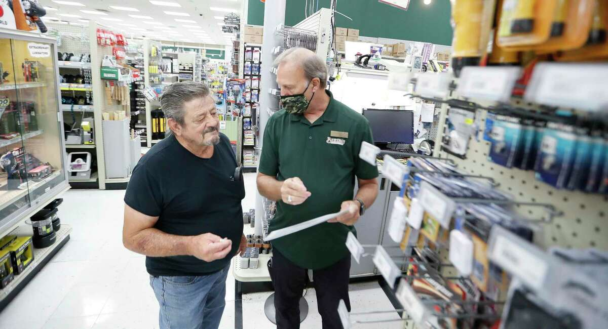 Customer Robert Turnbo, left, looks for a ceiling fan part without a mask on, as he was helped by employee Charles Plumb in the electrical area of Bering's Hardware and Gifts, Monday, May 17, 2021, in Houston. Bering's removed signs at its entrances saying masks are required, and increasingly more people are coming inside without them, its owner said.