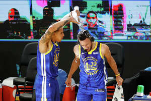Stephen Curry of the Golden State Warriors is doused with water by Juan Toscano-Anderson of the Golden State Warriors after their win over the Denver Nuggets at Chase Center on April 12, 2021.