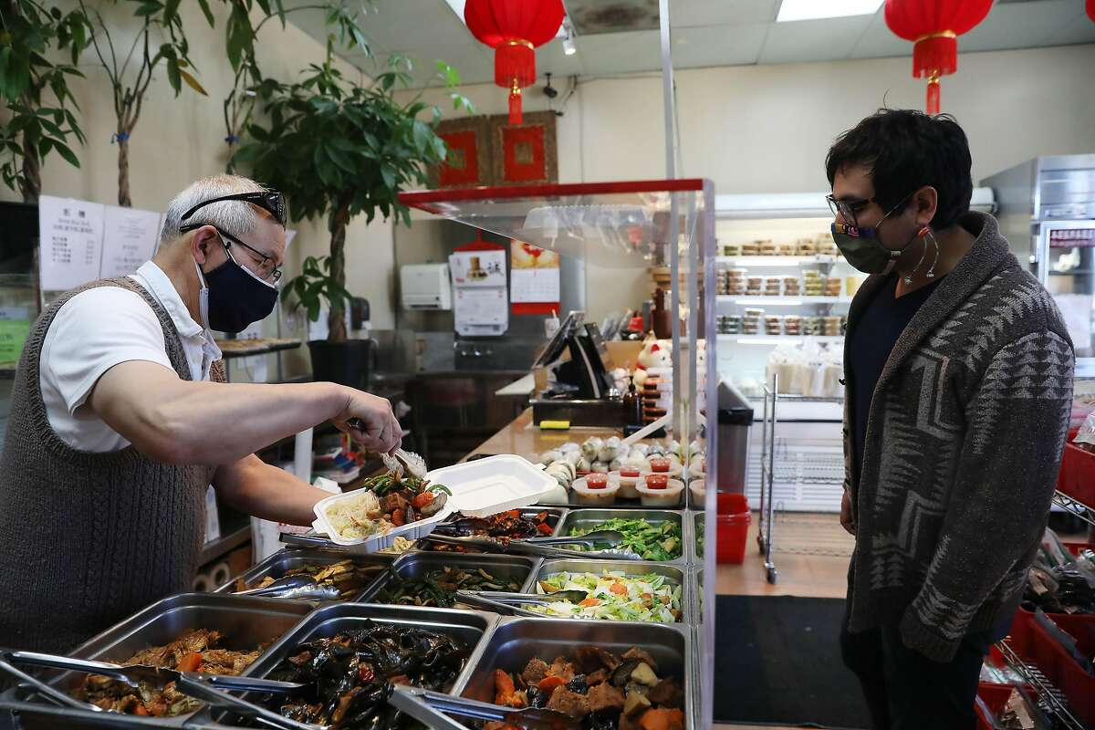Manager Steve Chung prepares a bento combination plate for customer Mick Vasquez of Saratoga at Sogo Tofu in San Jose.