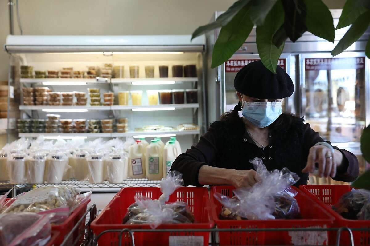 Assistant manager Aby Voigt organizes items for sale at Sogo Tofu in San Jose.