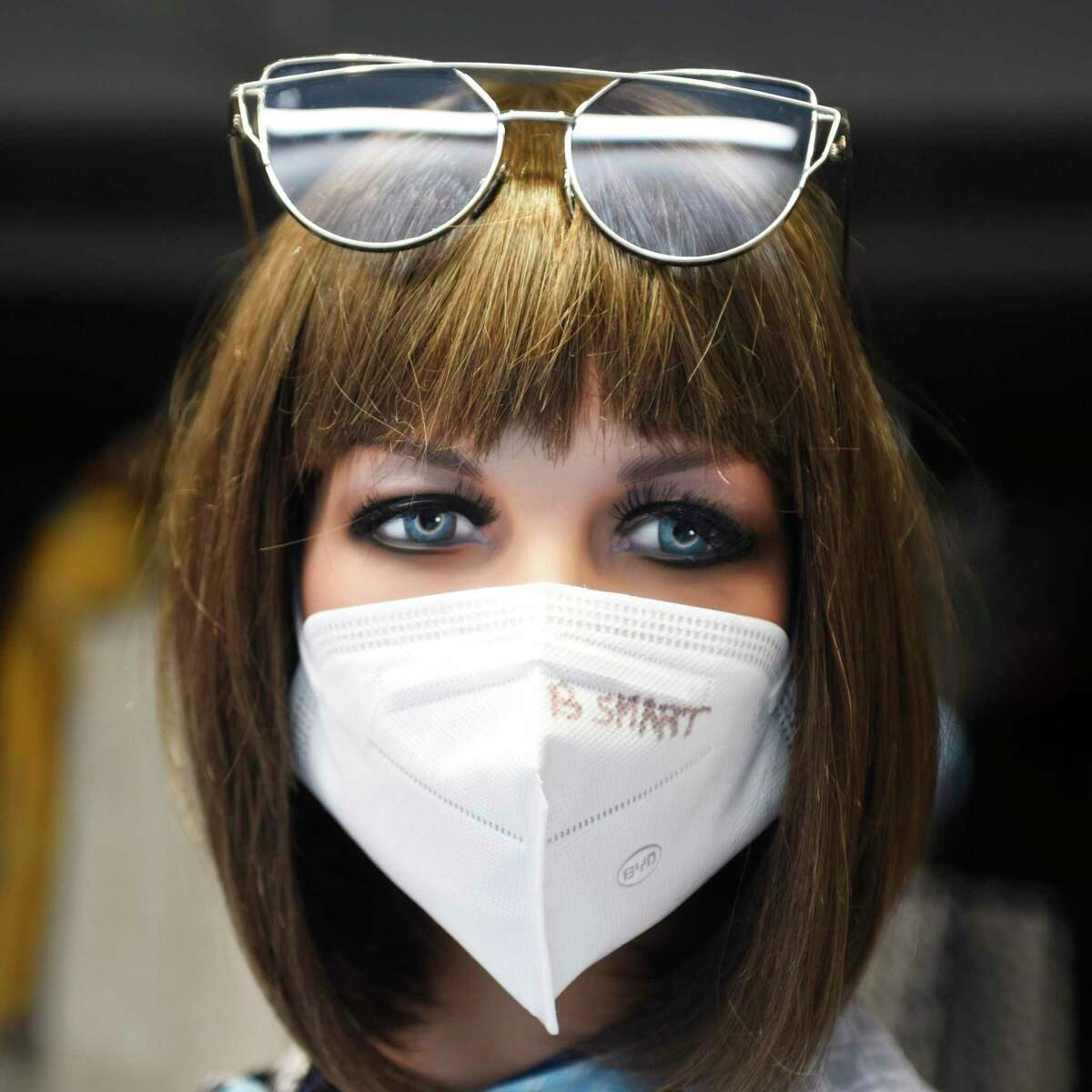"""Mannequins wear protective face masks with the message """"B Smart"""" in the window of OGGI 5 Boutique in Greenwich."""