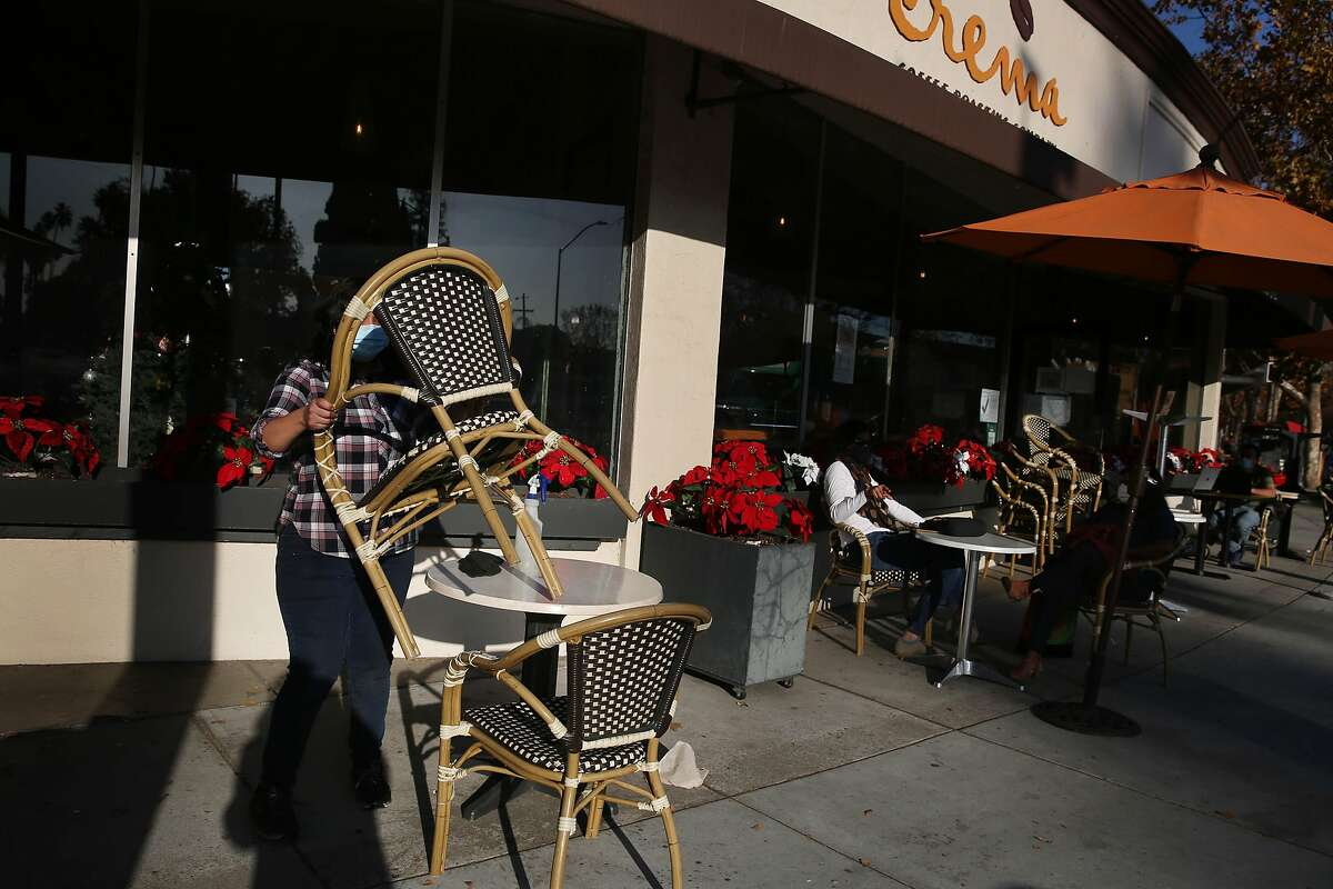 Barista Lizbeth Sanchez closes down the outdoor dining area at Crema on the Alameda in San Jose.