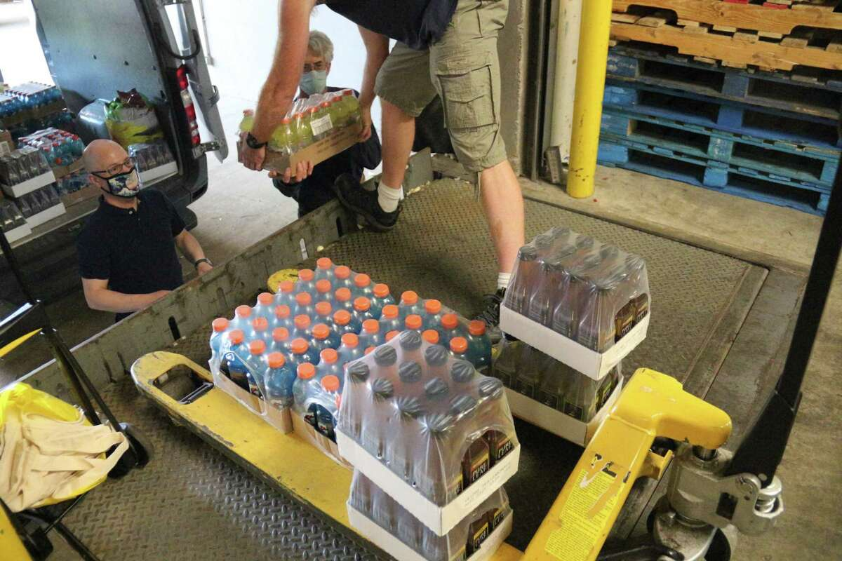 Vincent Contrucci, left, director of community service at Quinnipiac University, and Clayton Johnson, right, food reclamation manager for Master's Manna food pantry of Wallingford, load a van with food and beverages donated by Quinnipiac students on May 20.