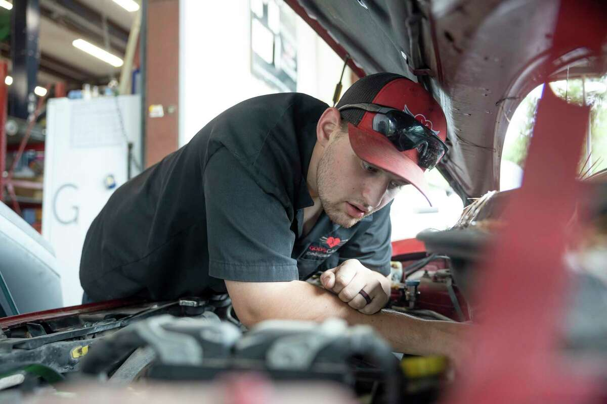 Thomas Morrison inspects the A/C unit of a vehicle at God's Garage, Friday, April 16, 2021, in Conroe. Since vaccination rollout God's Garage has seen an increase in volunteer signups.