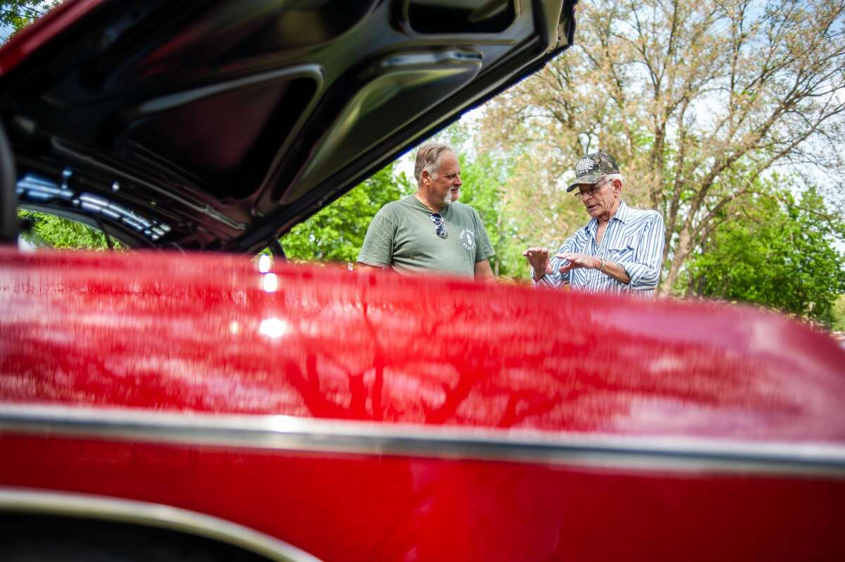 Caro resident Chris Knoll (left) chats with Dave Stout in front of Knoll's '68 Impala SS 427 at a car show on May 21, 2021 in Porte Park, Sanford. The car show was a part of the 'Sanford Rising