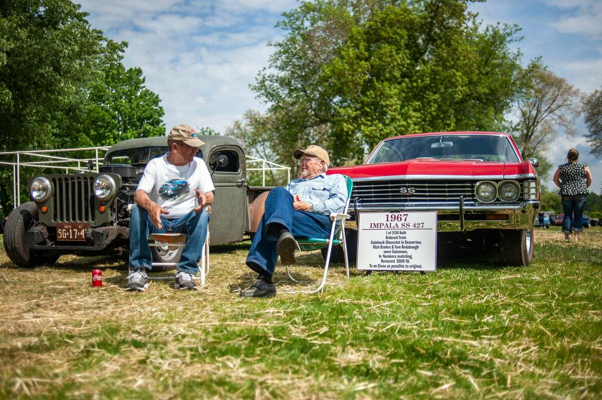 Beaverton residents Bill Illig (left) and Jack Giger sit in front of their'28 Chrysler Coup and '67 Impala respectively at a car show on May 21, 2021 in Porte Park, Sanford. The car show was a part of the 'Sanford Rising