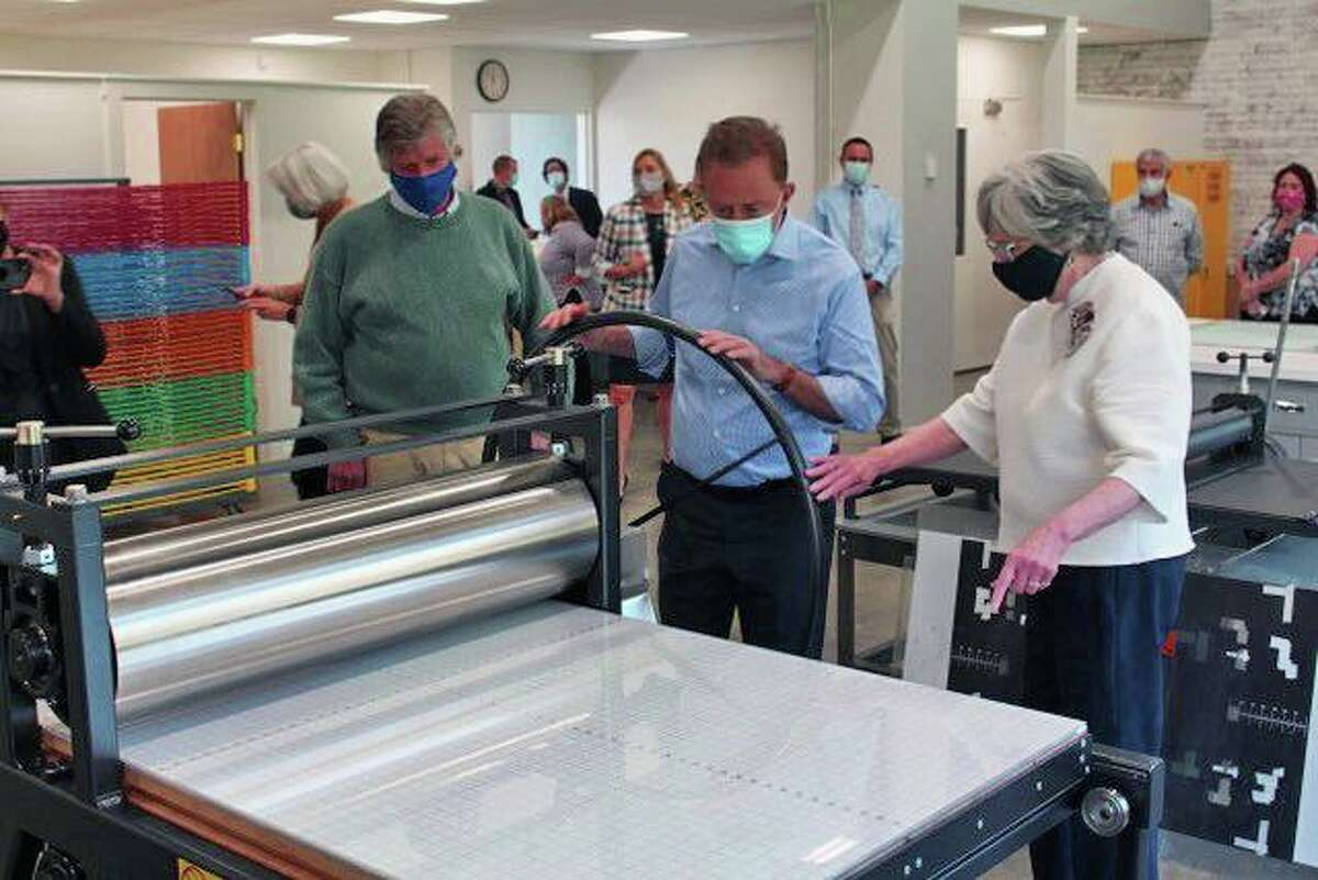 Gov. Ned Lamont, center, tries out the new printing press at Five Points Center for the Arts during his May 14 visit. He is pictured with the center's board president, Eric Forstmann, left, and executive director Judy McElhone.