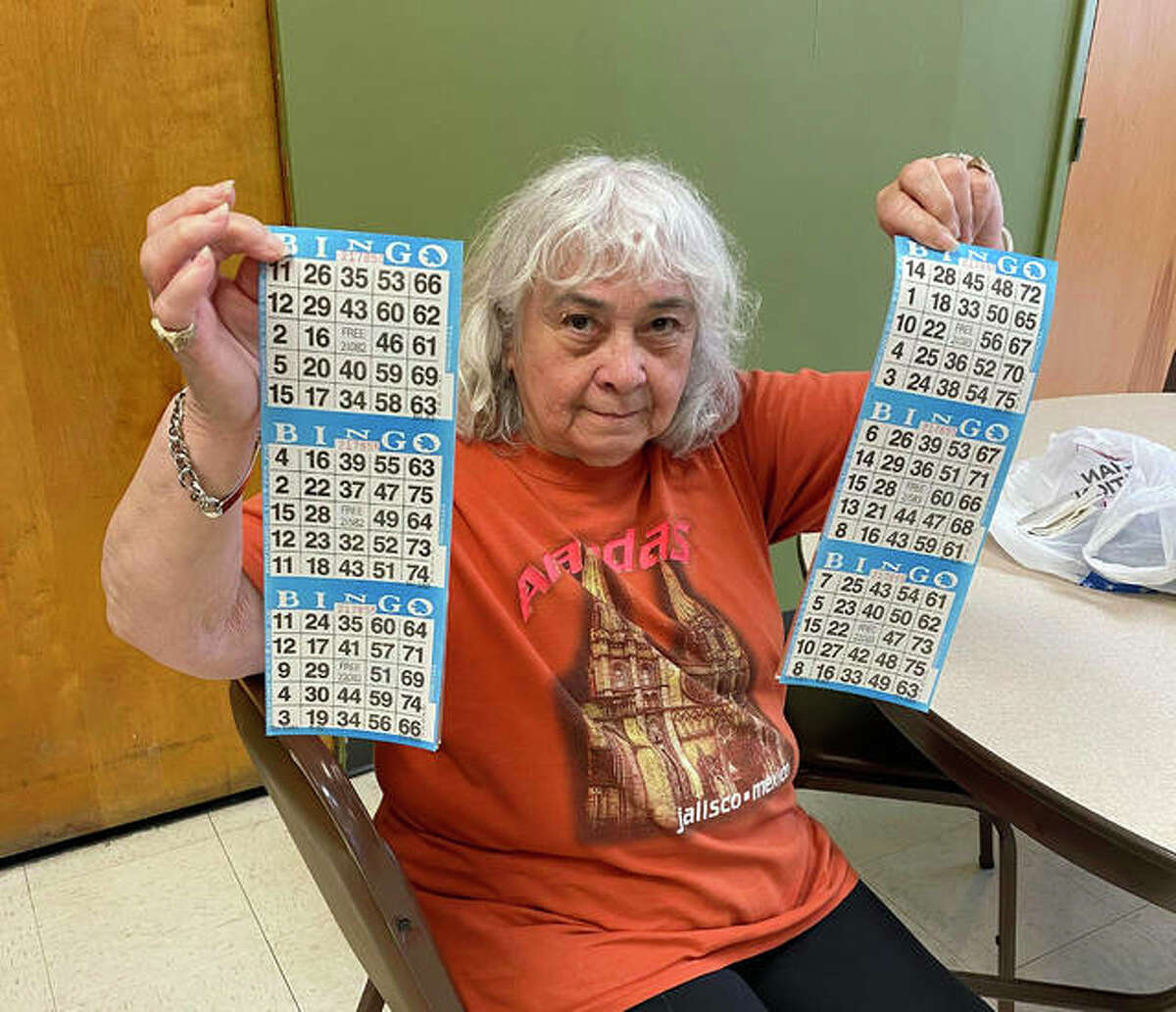 Helen, a Main Street Community Center client, shows her bingo cards during a Friday game at the center.