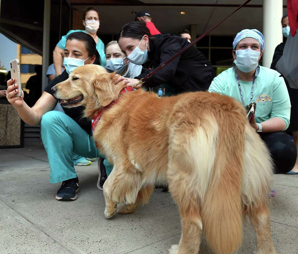 Tania Taft (far left) takes a selfie with therapy dog Reissa, a golden retriever, during a therapy dog parade at Yale New Haven Hospital in New Haven on May 21, 2021. Reissa is owned by Pat Reid of North Branford.