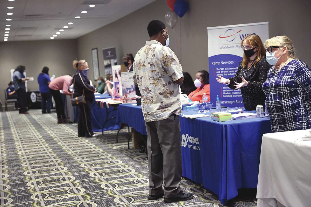 Recruiters looking to fill positions meet with candidates during a job fair. The recruiters were trying to fill full- and part-time positions and many are offering bonuses or attractive benefit packages to lure potential employees.