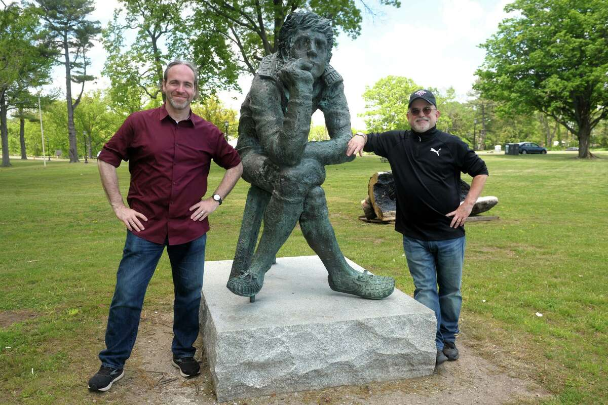 """Tom Evans and Jim Warren (left and right) pose next to a statue commonly referred to as """"the thinker"""" on the grounds of the former Shakespeare theater in Stratford, Conn. May 18, 2021. The theater was destroyed by fire in 2019. The two men are planning to build a replica of Shakespeare's Globe theater on the grounds."""