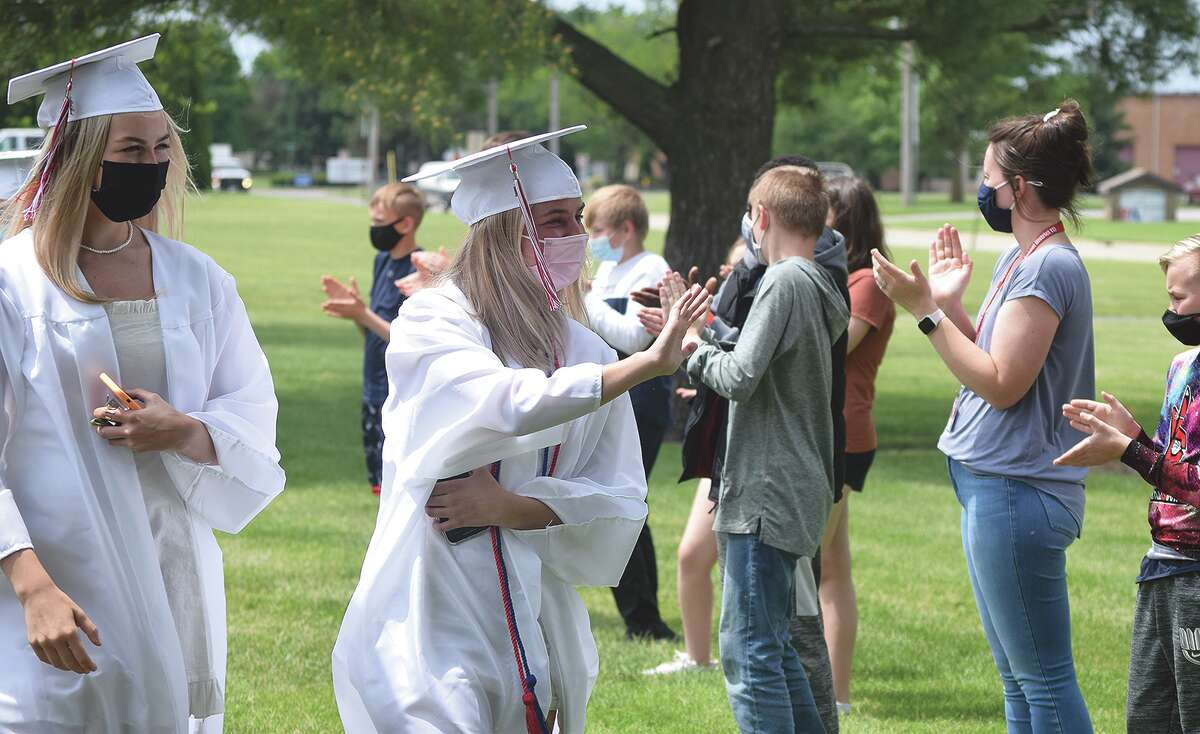 Seniors Amelia Pine (left) and Claire Van Aken wave Friday at Eisenhower Elementary School students during the school's