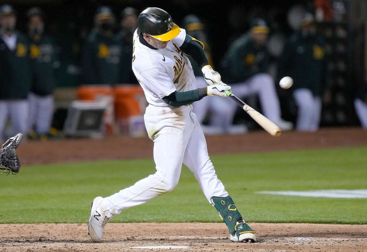 OAKLAND, CALIFORNIA - MAY 18: Mark Canha #20 of the Oakland Athletics hits a sacrifice fly scoring Jed Lowrie #8 against the Houston Astros in the seventh inning at RingCentral Coliseum on May 18, 2021 in Oakland, California. (Photo by Thearon W. Henderson/Getty Images)