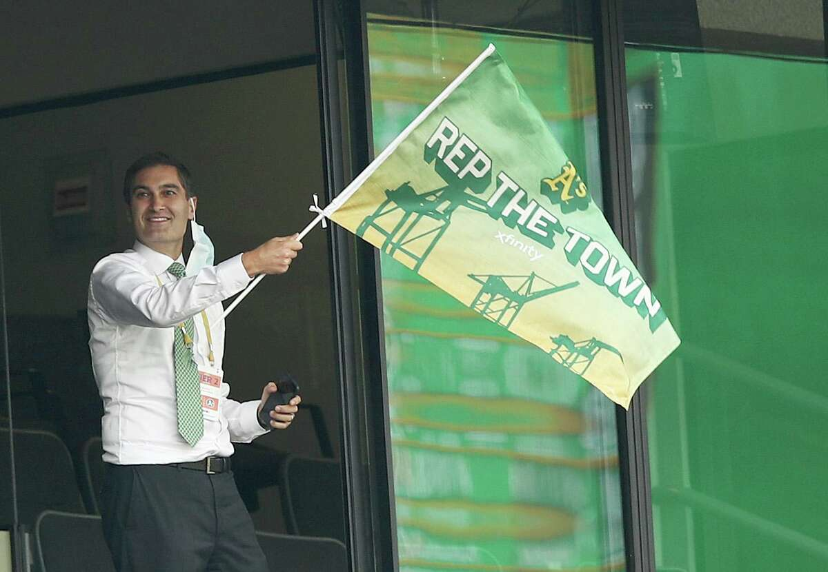 OAKLAND, CALIFORNIA - OCTOBER 01: Oakland Athletics team president Dave Kaval waves a flag after they tied their game against the Chicago White Sox in the fourth inning of Game Three of the American League wild card series at RingCentral Coliseum on Oct