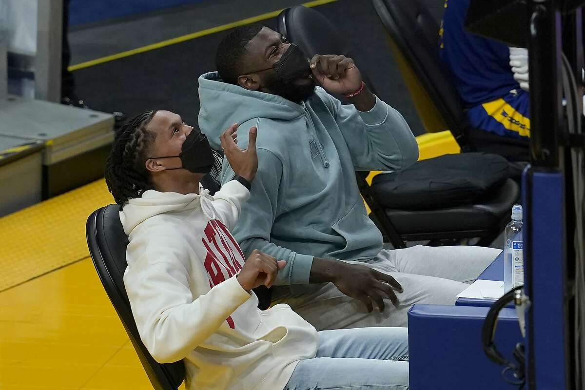 Golden State Warriors' Damion Lee, left, who is sidelined after contracting COVID-19 despite being vaccinated, sits on the sideline with injured Eric Paschall during the second half of an NBA basketball game against the Utah Jazz in San Francisco, Monday, May 10, 2021. (AP Photo/Jeff Chiu)