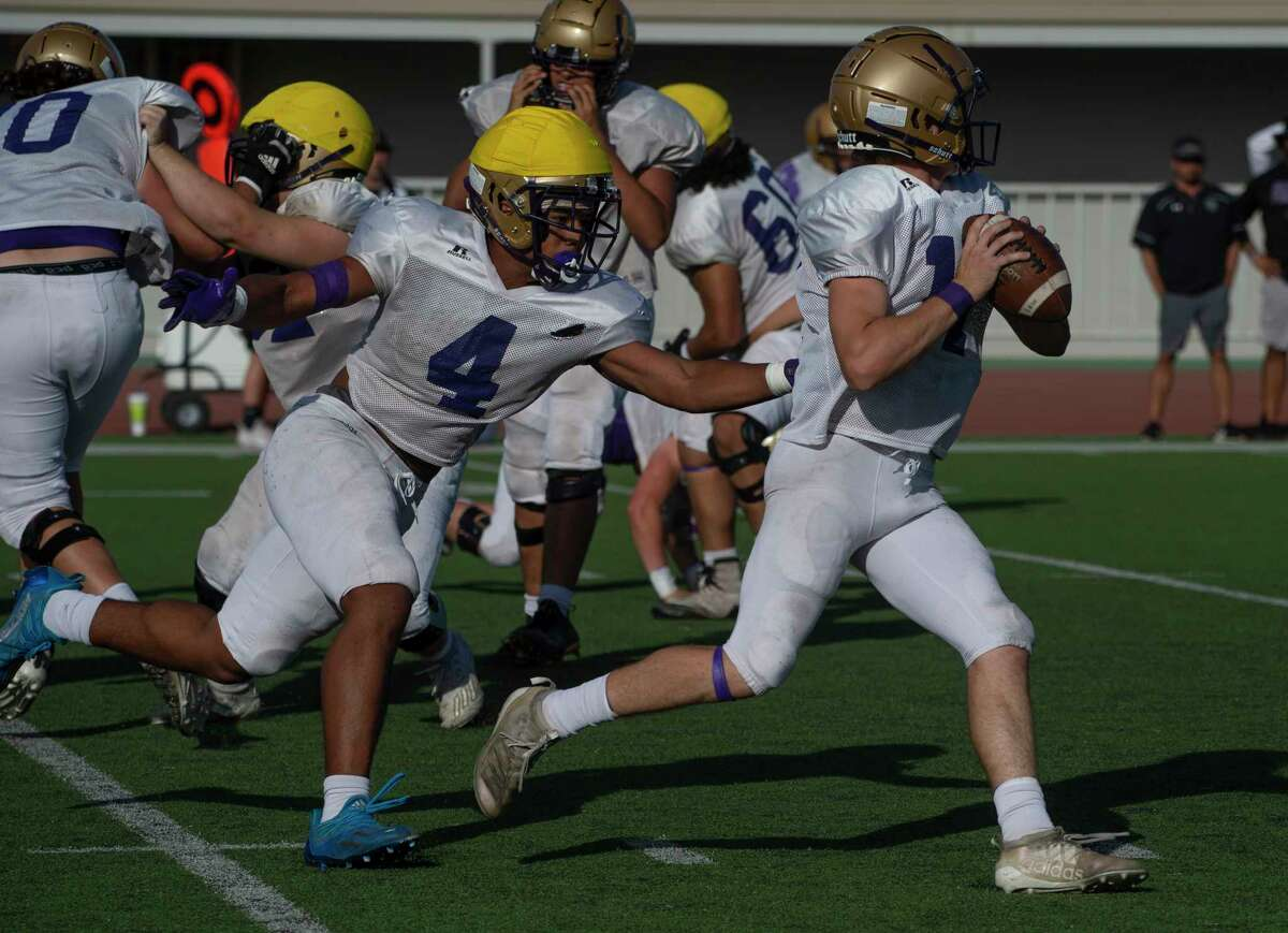 Midland High's Jake Cunningham is chased out of the pocket by Matteo Houston 5/21/2021 during the spring game at Doc Dodson Memorial Stadium. Tim Fischer/Reporter-Telegram