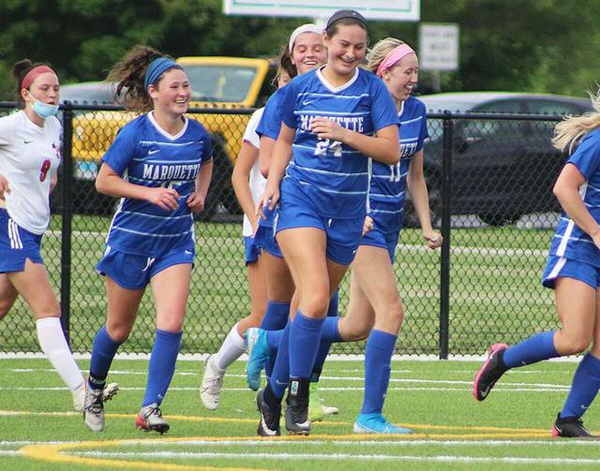 Marquette's Madelyn Smith (15), Anna Rogers (24) and Kylie Murray (11) celebrate a goal Friday against Roxana at Gordon Moore Park, while the Shells' Lorali Copeland (9 at far left) heads back upfield. Marquette handed the Shells their first loss of the season 8-2.