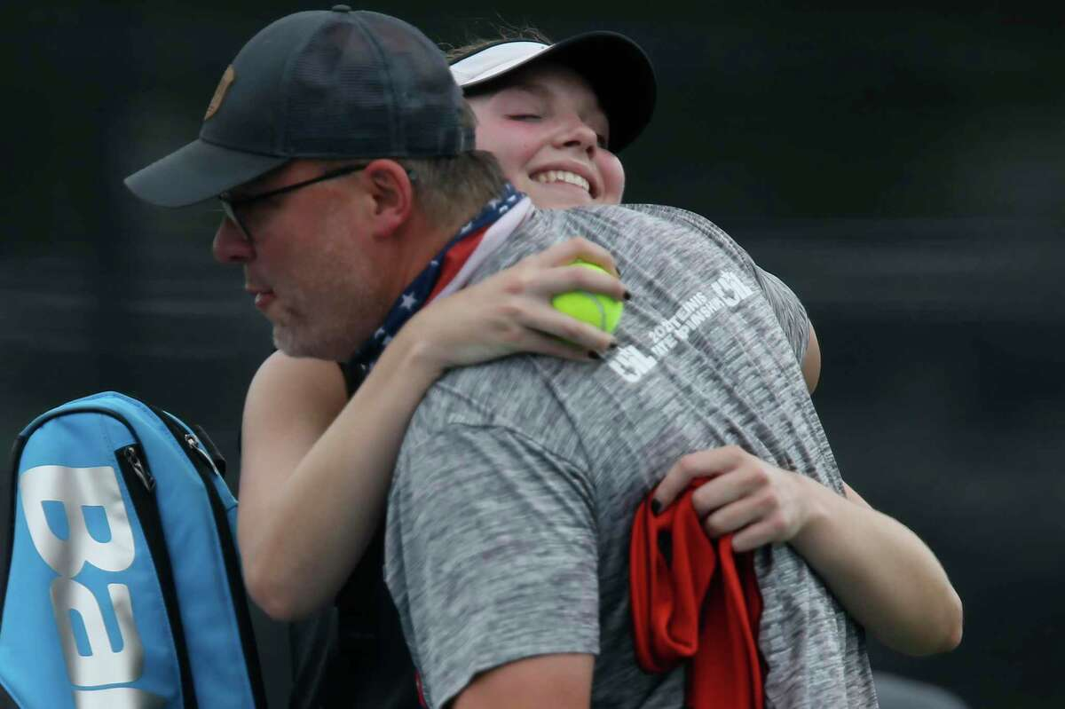 Devine's Brooke Runyan hugs head coach Mark Feltner after defeating Gatesville's Stormy Tatum for the state title in the UIL District 4A Championships at Northside Tennis Center, Friday, May 21, 2021. Runyan took the title, 6-3, 6-4.