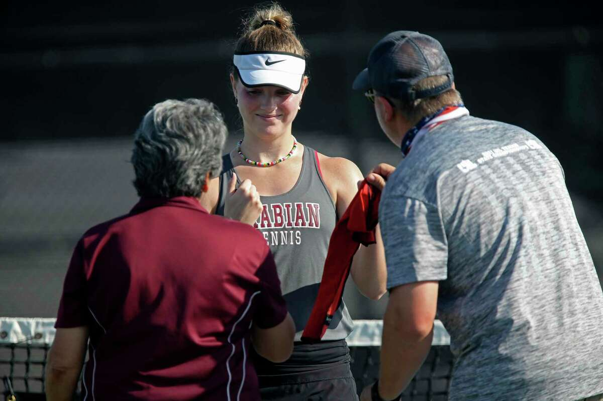 Devine?•s Brooke Runyan smiles as she talks with coaches Kandi Darnell and Mark Feltner during her match against Gatesville?•s Stormy Tatum in the UIL District 4A State Championships at Northside Tennis Center, Friday, May 21, 2021. Runyan went on to win the state championship, 6-3, 6-4.