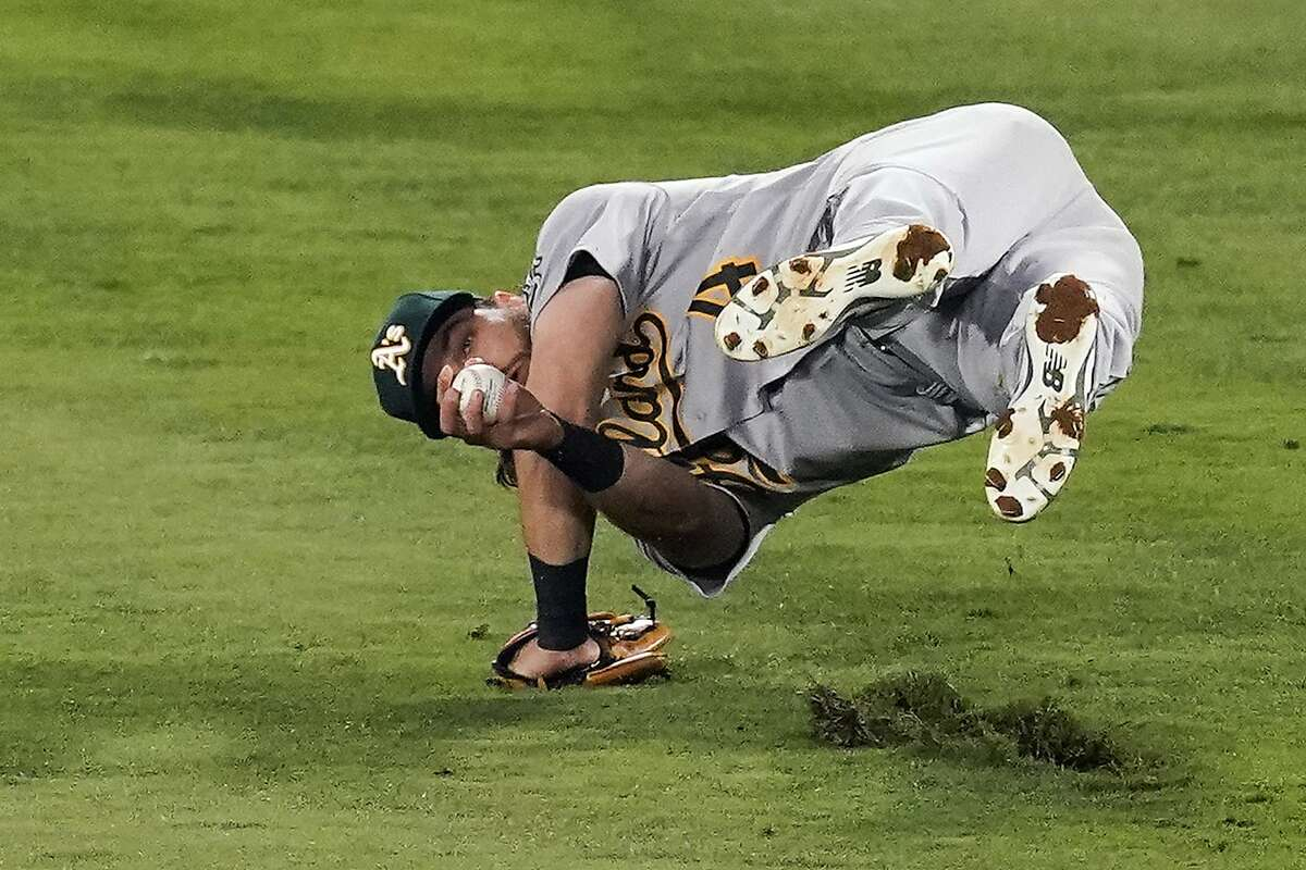 Oakland Athletics second baseman Chad Pinder (4) holds on to the ball while rolling to catch a fly ball hit by Los Angeles Angels' Jose Iglesias (4) during the fifth inning of a baseball game Friday, May 21, 2021, in Anaheim, Calif. (AP Photo/Ashley Landis)