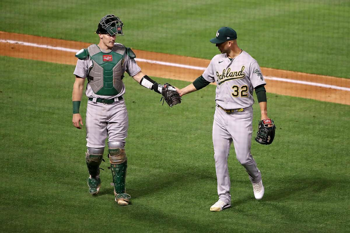 ANAHEIM, CALIFORNIA - MAY 21: James Kaprielian #32 and Sean Murphy #12 of the Oakland Athletics walk to the dugout at the end of the fifth inning against the Los Angeles Angels at Angel Stadium of Anaheim on May 21, 2021 in Anaheim, California. (Photo by Katelyn Mulcahy/Getty Images)