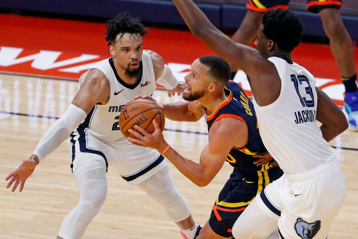 Golden State Warriors' Stephen Curry drives between Memphis Grizzlies' Jaren Jackson, Jr. and Dillon Brooks during 3rd quarter of NBA Play-In Tournament game at Chase Center in San Francisco, Calif., on Thursday, May 20, 2021.