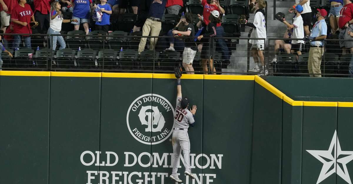 Houston Astros right fielder Kyle Tucker leaps but is well short of a three-run home run hit by Texas Rangers' Adolis Garcia during the 10th inning of a baseball game in Arlington, Texas, Friday, May 21, 2021. The Rangers won 7-5. (AP Photo/Tony Gutierrez)