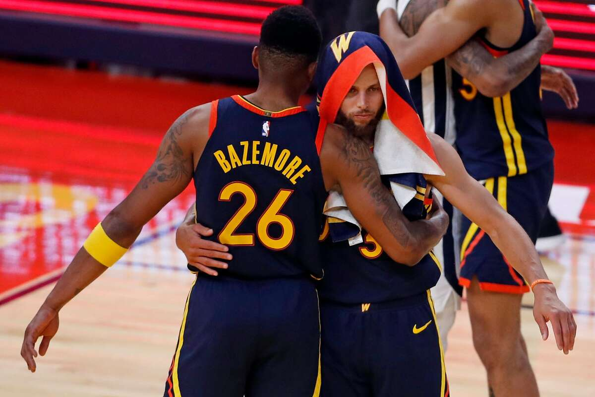 Golden State Warriors' Stephen Curry and Kent Bazemore embrace after Memphis Grizzlies' 117-112 win in overtime in NBA Play-In Tournament game at Chase Center in San Francisco, Calif., on Friday, May 21, 2021.