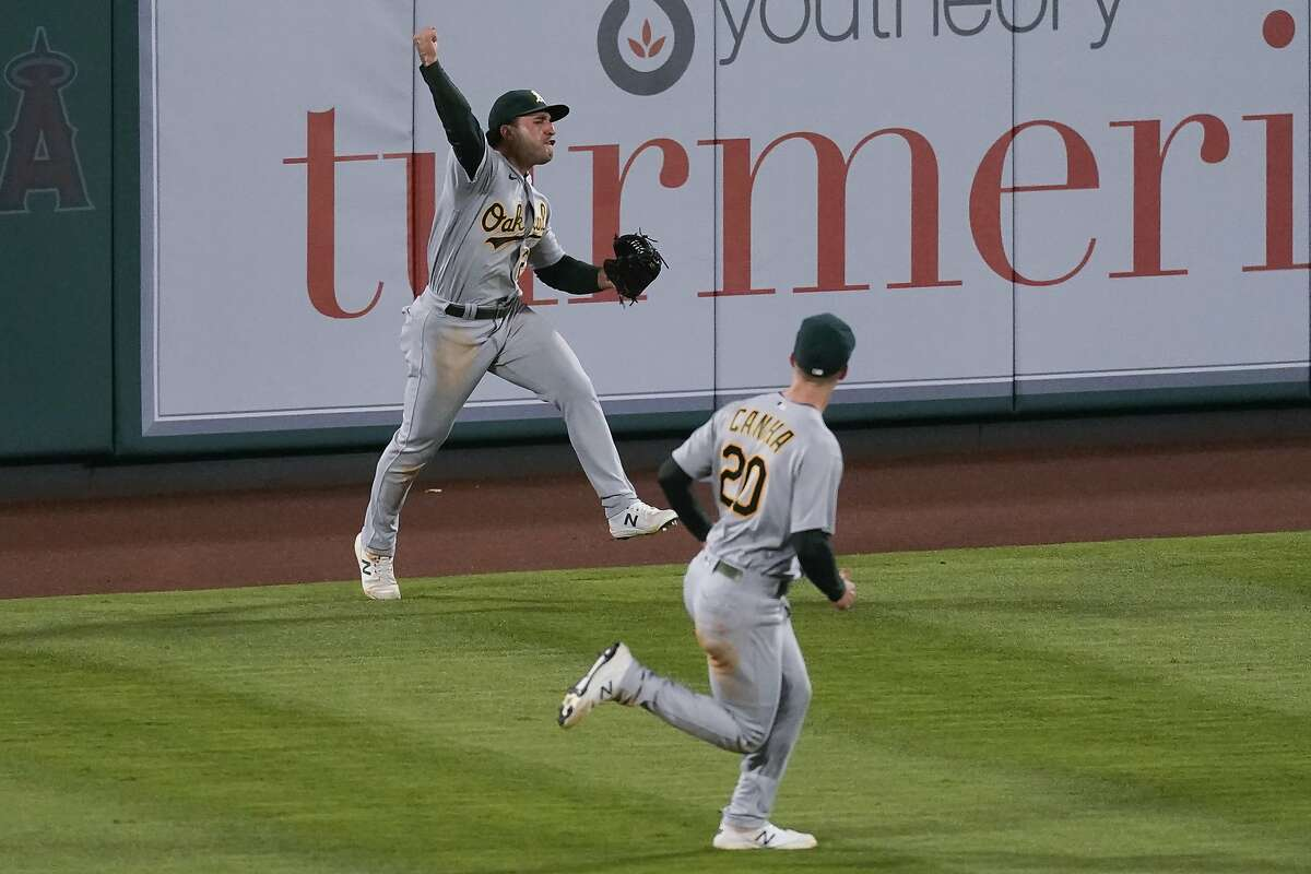 Oakland Athletics center fielder Ramon Laureano, left, celebrates after catching a fly ball hit by Los Angeles Angels' Anthony Rendon during the seventh inning of a baseball game Friday, May 21, 2021, in Anaheim, Calif. Oakland Athletics left fielder Mark Canha (20) is at right. (AP Photo/Ashley Landis)