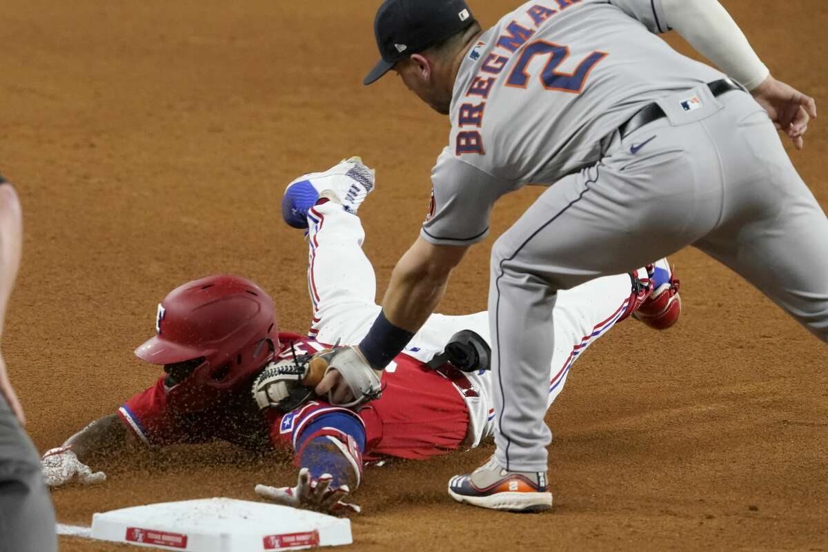 Texas Rangers' Adolis Garcia is tagged out at third by Houston Astros' Alex Bregman (2) as Garcia tried to stretch a two-run double during the fourth inning of a baseball game in Arlington, Texas, Friday, May 21, 2021. (AP Photo/Tony Gutierrez)