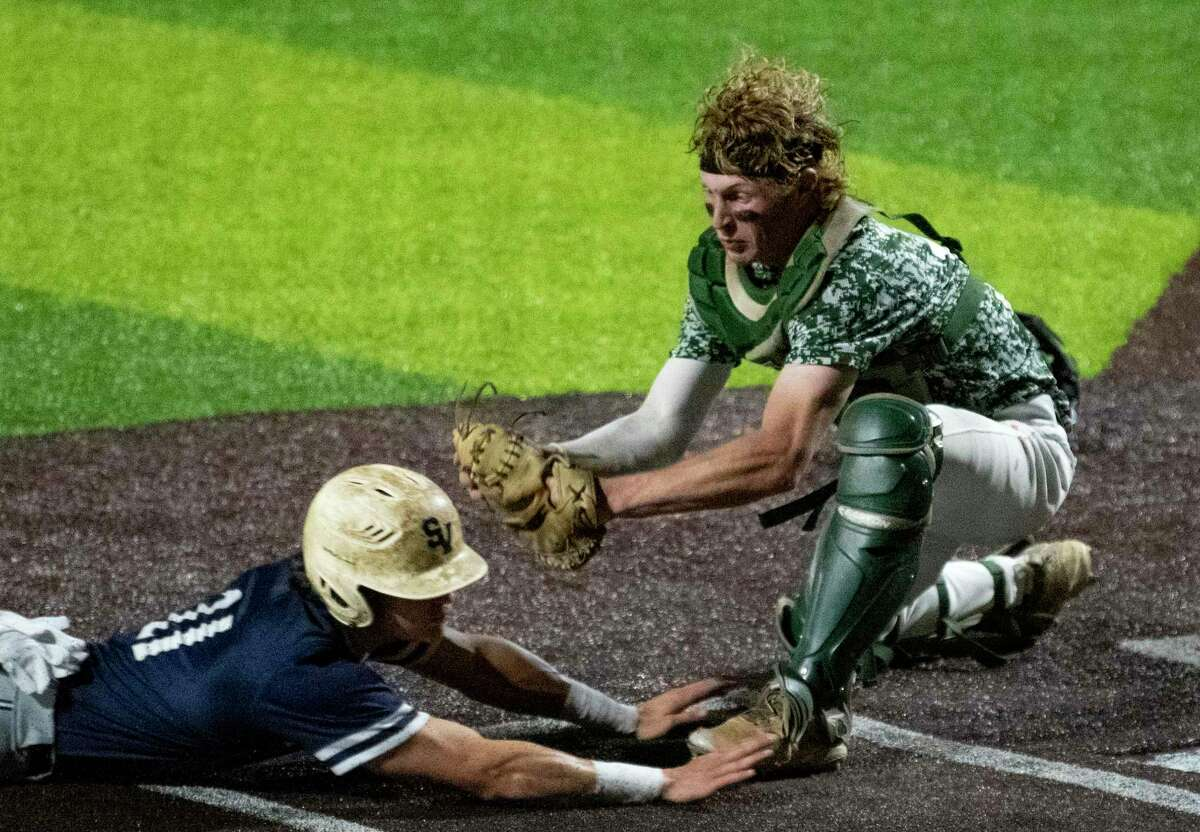 Reagan catcher Ryan Beaird tags out Christian Keller of Smithson Valley during the sixth inning of Game 2 of the 6A regional quarterfinal series at North East Sports Park on Friday, May 21, 2021. Reagan won, 4-1.