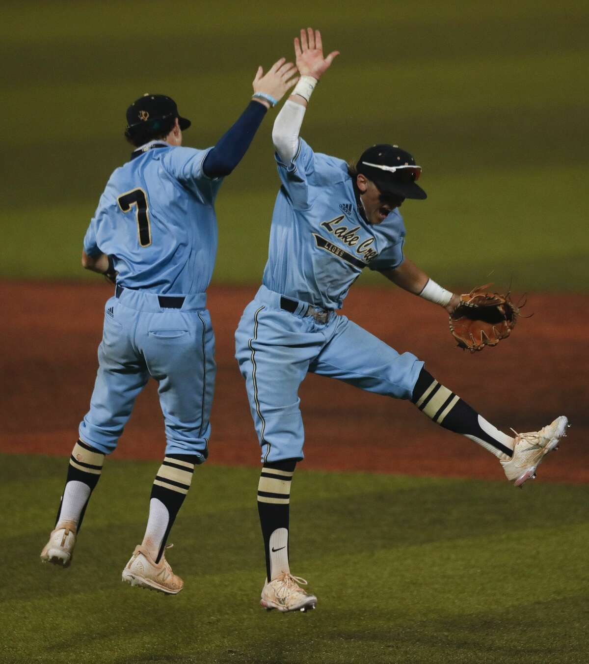 Lake Creek second baseman Jaron Lyness (9) celebrates with shortstop Blake Brown (7) after the team's 12-7 8th-inning win over Montgomery in Game 2 of a high school baseball Region II-6A quarterfinal series at Sam Houston State University, Friday, May 21, 2021, in Huntsville.