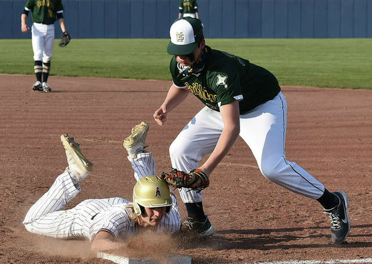 In this file photo, Father McGivney's Gabe Smith applies the tag for an out at first base during a game against East Alton-Wood River earlier this season. On Friday, Smith threw seven scoreless innings in a nine-inning loss to Mount Olive.