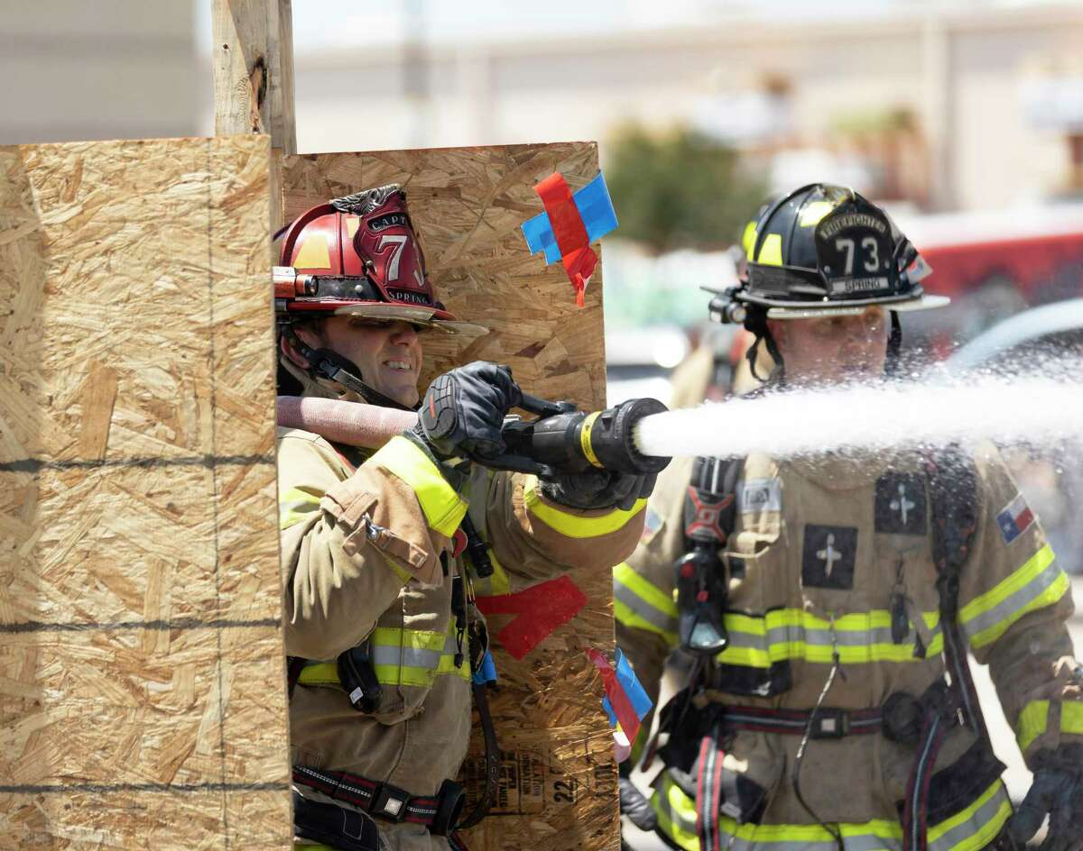 Larry Wilkinson from Spring Fire Station 76, left, competes in the hose drag challenge during the 3rd annual North Harris Firefighter Challenge, Saturday, April 24, 2021, in Spring. Over 10 fire departments in the Greater Houston Area have competed in the past 3 years. Team compete by completing timed firefighter training tasks such as, hose hoist, forced entry and dummy drag rescue.