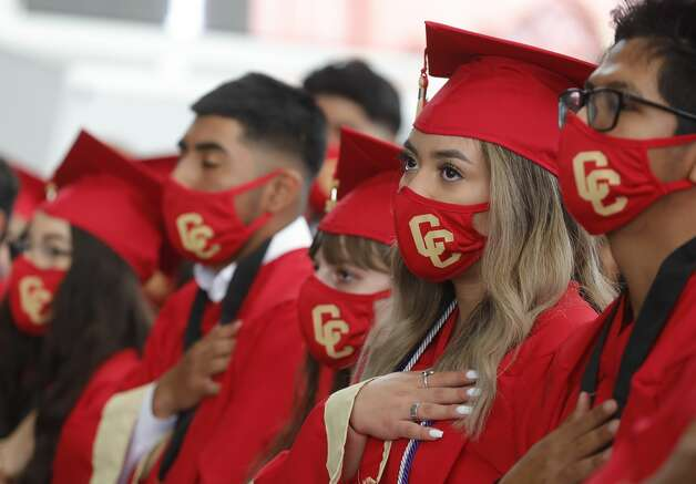 Caney Creek students wear custom face-masks as the national anthem is played during a graduation ceremony at Cynthia Woods Mitchell Pavilion, Saturday, May 22, 2021, in The Woodlands. Photo: Jason Fochtman/Staff Photographer / 2021 © Houston Chronicle