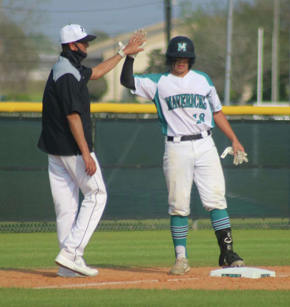 Pasadena Memorial head coach Terry Garza, the District 22-6A Baseball Coach of the Year, greets a Maverick at third base. Garza guided the Mavs to an 11-game district winning streak this spring.