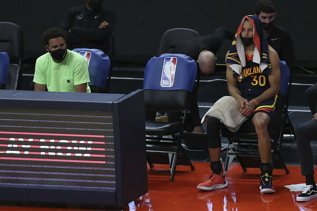 Golden State Warriors' Stephen Curry, right and Klay Thompson sit during a timeout in the first half of an NBA basketball Western Conference play-in game against the Memphis Grizzlies in San Francisco, Friday, May 21, 2021. (AP Photo/Jed Jacobsohn)
