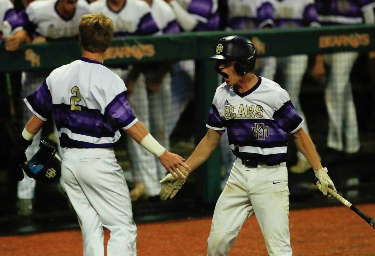 Montgomery's Trey Acreman, left, gets a high-five from Connor Benge after scoring on wild pitch by Lake Creek starting pitcher Shane Sdao in the first inning of Game 2 of a high school baseball Region II-6A quarterfinal series at Sam Houston State University, Friday, May 21, 2021, in Huntsville.