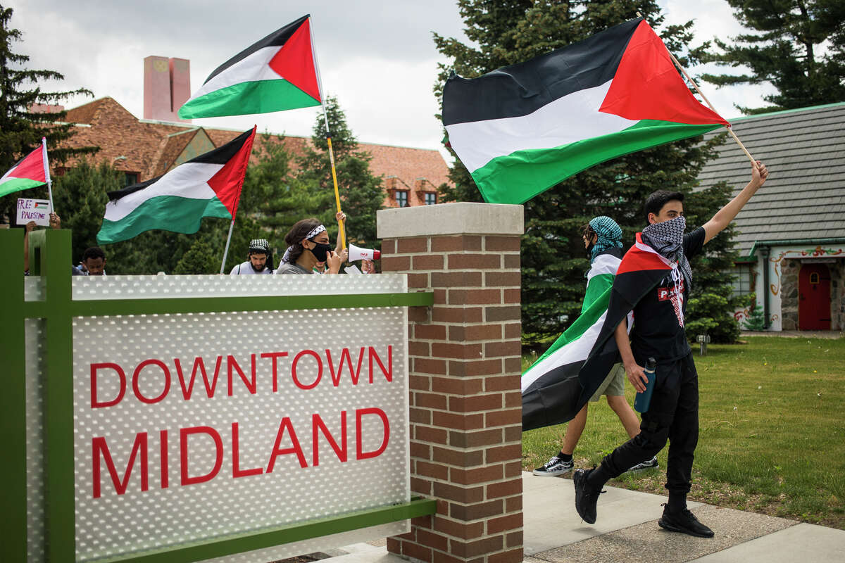 Salem Al-Ahmed, right, carries a Palestinian flag as approximately 150 people gather for a rally and march in solidarity with Palestine Saturday, May 22, 2021 in downtown Midland. (Katy Kildee/kkildee@mdn.net)