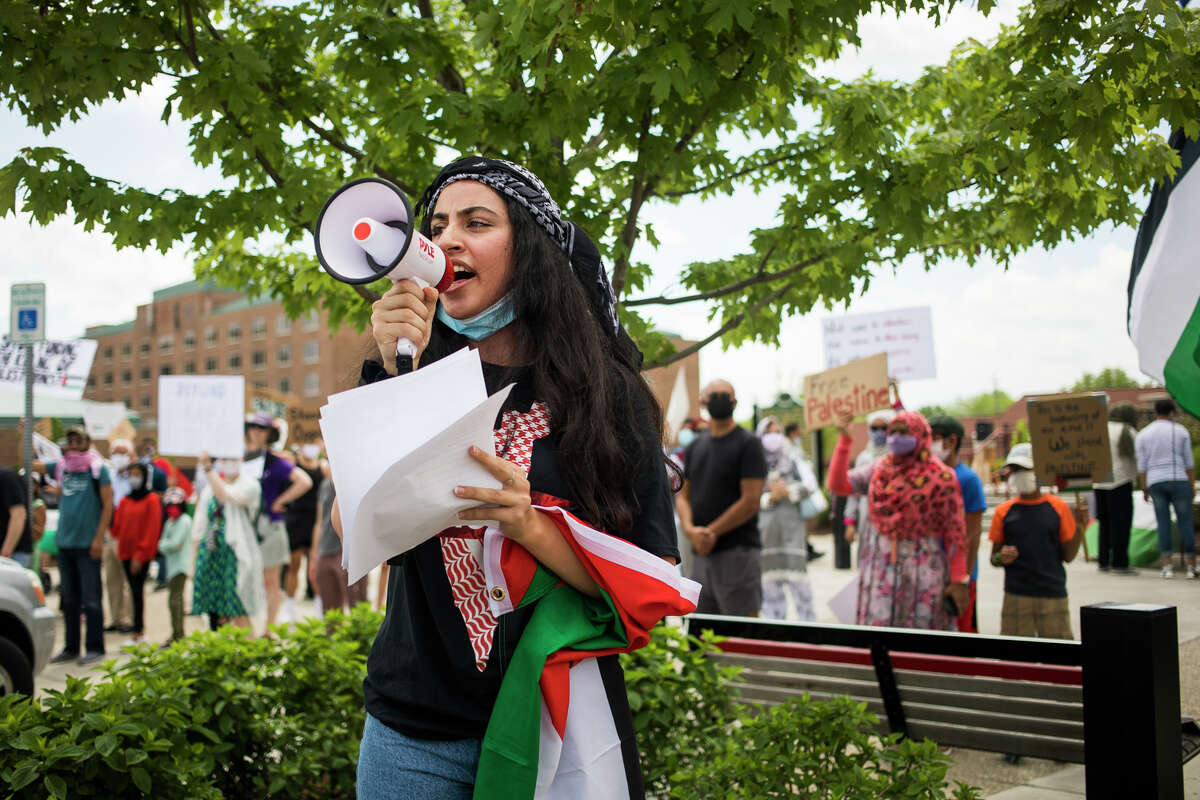 Reem Al-Ahmad of Midland recites a chant through a megaphone as approximately 150 people gather for a rally and march in solidarity with Palestine Saturday, May 22, 2021 in downtown Midland. (Katy Kildee/kkildee@mdn.net)