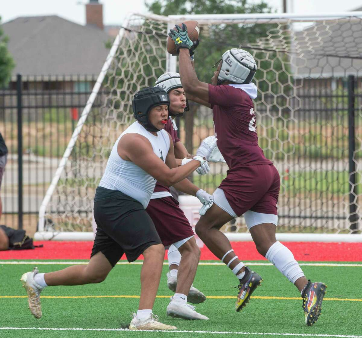 Lee High's Makhilyn Young grabs a pass on a crossing pattern in front of a Lubbock High defender 5/22/2021 in the championship 7-on-7 football game on the auxiliary fields at Scharbauer Sports Complex. Tim Fischer/Reporter-Telegram
