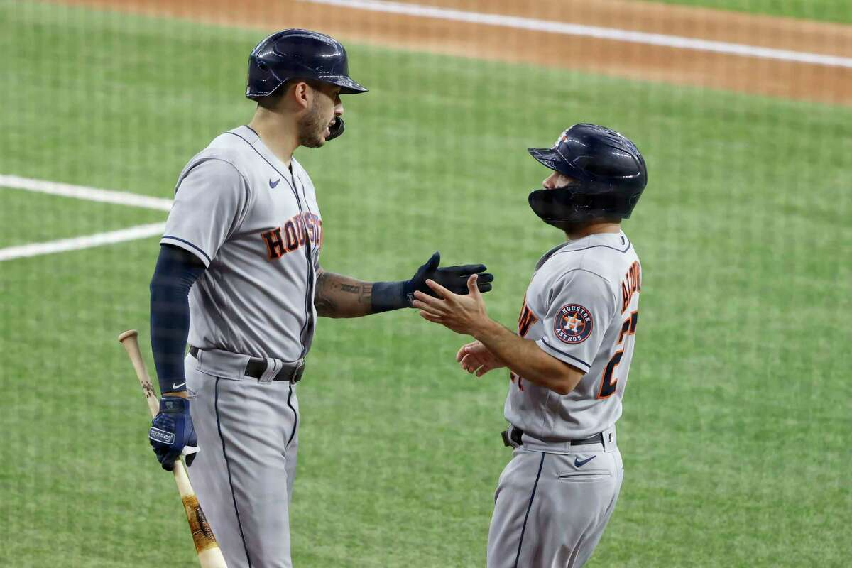 Houston Astros' Carlos Correa, left, congratulates Jose Altuve, right, after Altuve scored on a fielder's choice during the first inning of a baseball game against the Texas Rangers, Saturday, May 22, 2021, in Arlington, Texas. (AP Photo/Michael Ainsworth)
