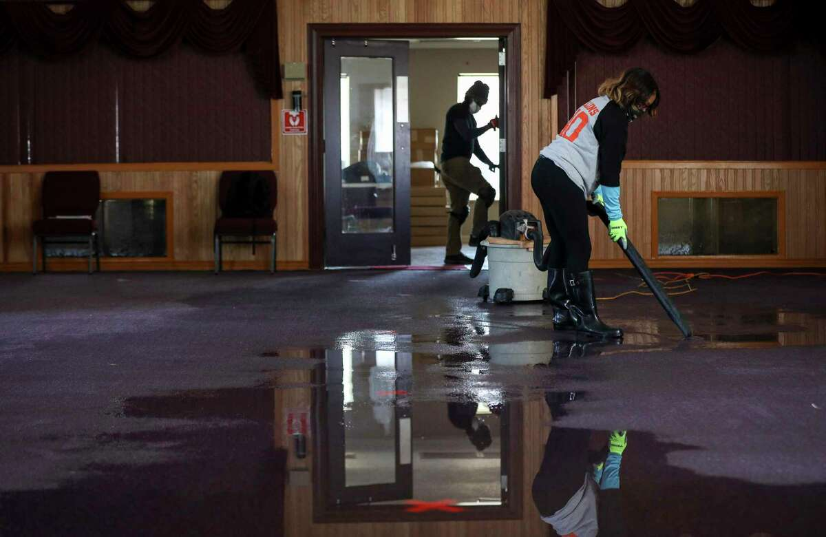 Lisa Collins, right, and her son Ossume work to clean up water from a busted pipe Saturday, Feb. 20, 2021, at Ebenezer United Methodist Church in Houston.