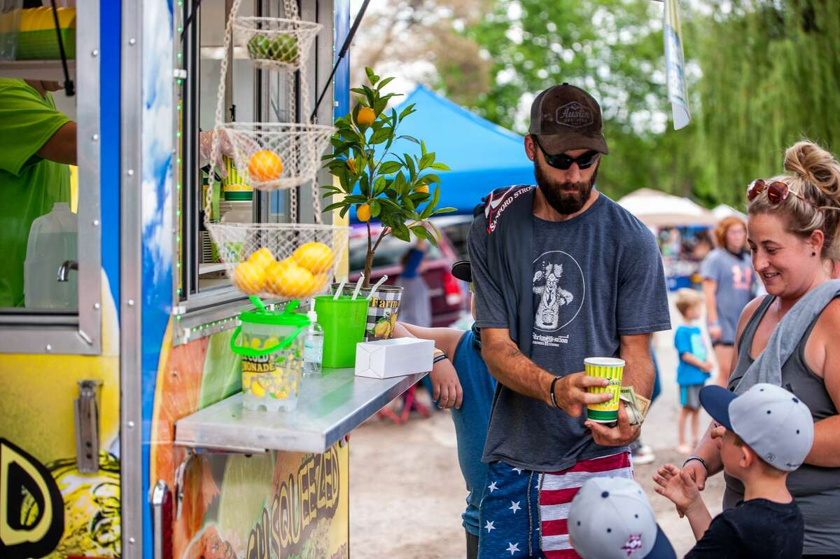 A family buys lemonade at the Sanford Rising event on Saturday, May 22, 2021.